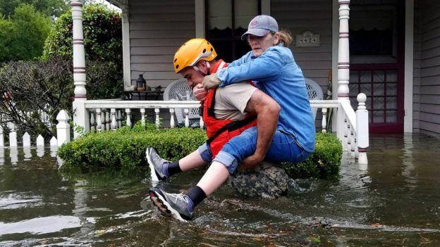 Un rescatista carga a una mujer en medio de una inundación tras el paso de la tormenta Harvey en Texas (EE.UU.)