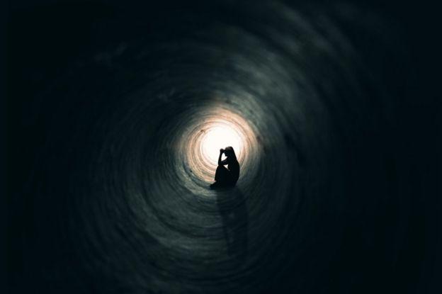Silueta de una mujer sentada en un túnel