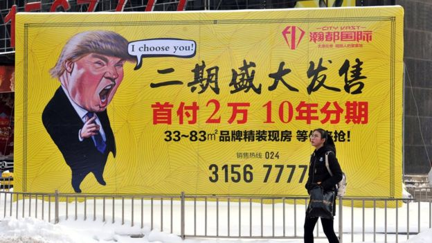 A pedestrian walks past a real estate advertisement featuring a cartoon figure of President Donald Trump in Shenyang in north-eastern China's Liaoning province. 22 Feb 2017.