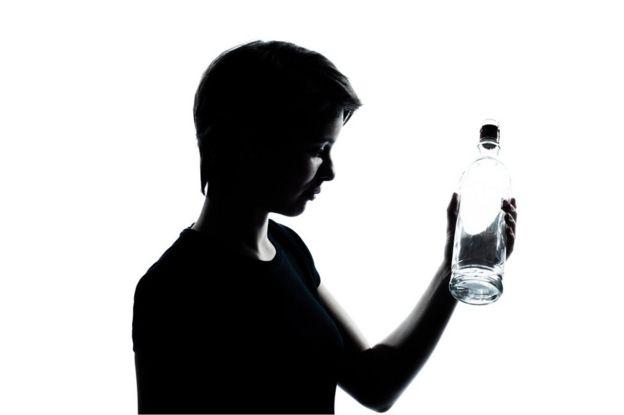 Joven mira a una botella vacía.