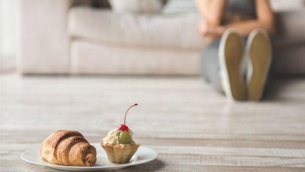 Un croissant y un cupcake con una mujer en el fondo