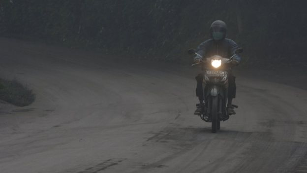A motorist rides his motorbike during a shower of ash and rain from Mount Agung volcano during an eruption in Bebandem Village, Karangasem, Bali, Indonesia 26 November 2017, in this photo taken by Antara Foto.