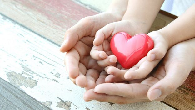As mãos de um adulto e de uma criança seguram a figura de um coração