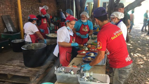 Volunteers serve food to people in a church in Cúcuta