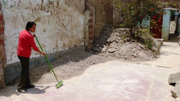 Natividad de la Cruz sweeps the dust in what used to be her house in Moyopampa