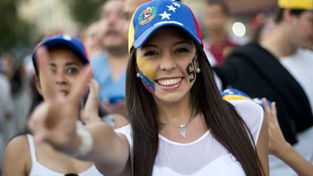 Una mujer sonríe en una manifestación de la oposición venezolana.