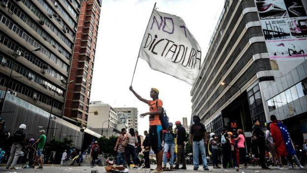 Joven venezolano con una bandera que dice: