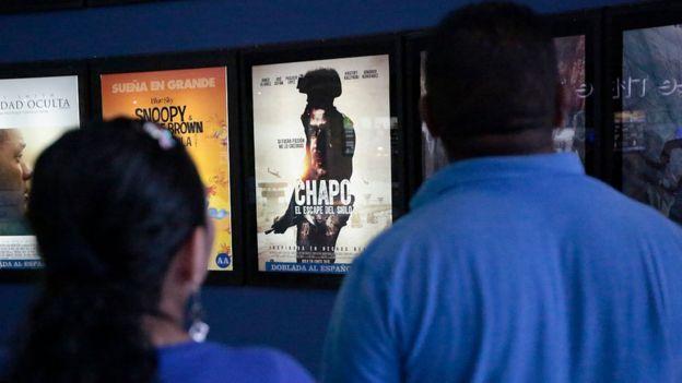 Una pareja frente a la cartelera de un cine de Acapulco, México.