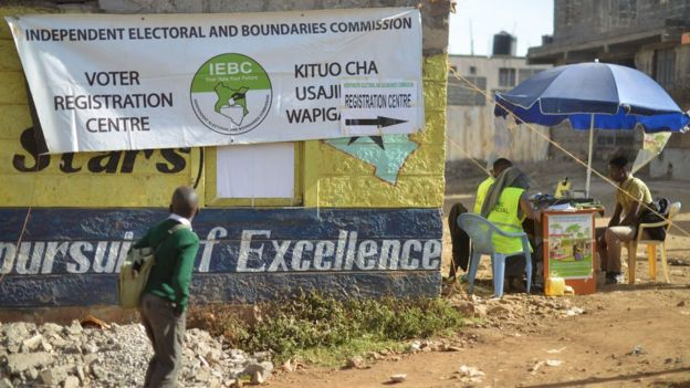A school boy looks at a banner advertising a voter-registration point January 18, 2017 as he walks past as Interim Electoral and Boundaries Commission (IEBC) clerks capture the biometric details of a voter at Baba-Dogo slum area of Nairobi.