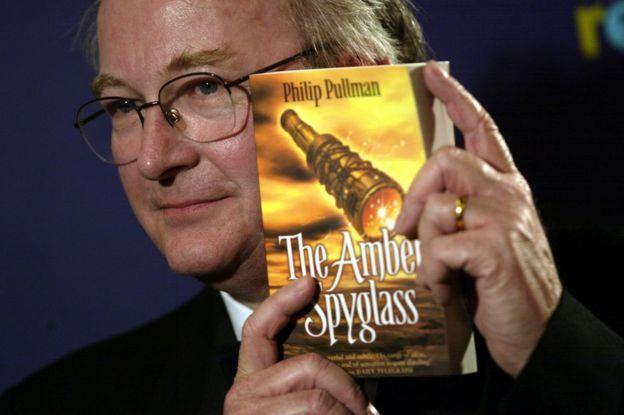 Philip Pullman con la portada de The Amber Spyglass