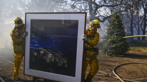 Firefightersremove a painting as they continue to extinguish fires in a home during the