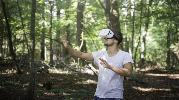 Un chico con unas gafas de realidad virtual en el bosque