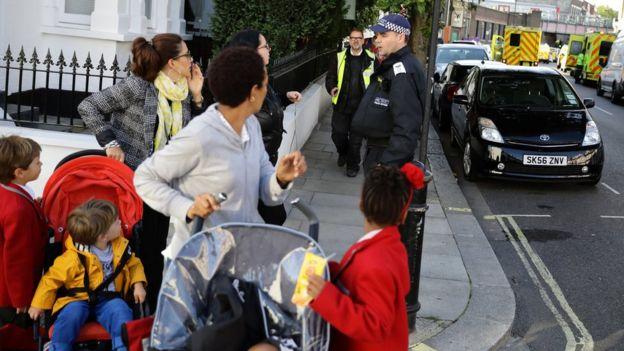 Policiais e mulheres empurrando carrinho de bebê nas proximidades da estação de Parsons Green