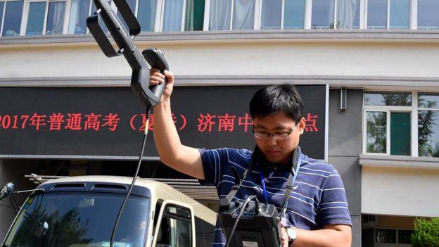 一名济南市无线电管理办公室的工作人员使用便携式电磁监测设备,对考点的电磁环境进行监测。