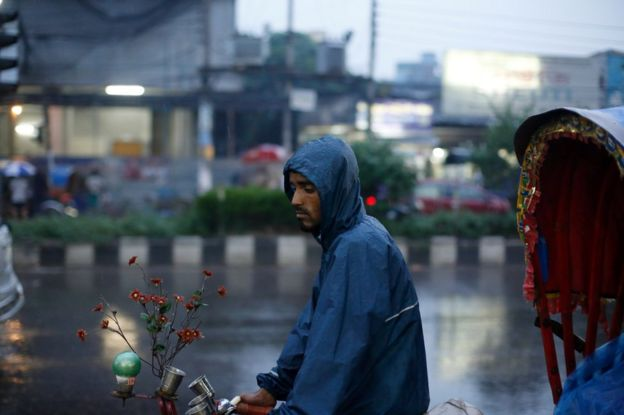 A rickshaw puller waits for passengers during rainy weather in the streets in Dhaka, Bangladesh, 29 May 2017.