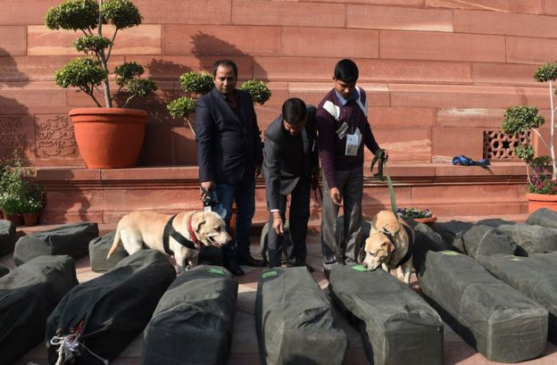 Indian security personnel check bags containing budget documents outside Parliament House in capital Delhi