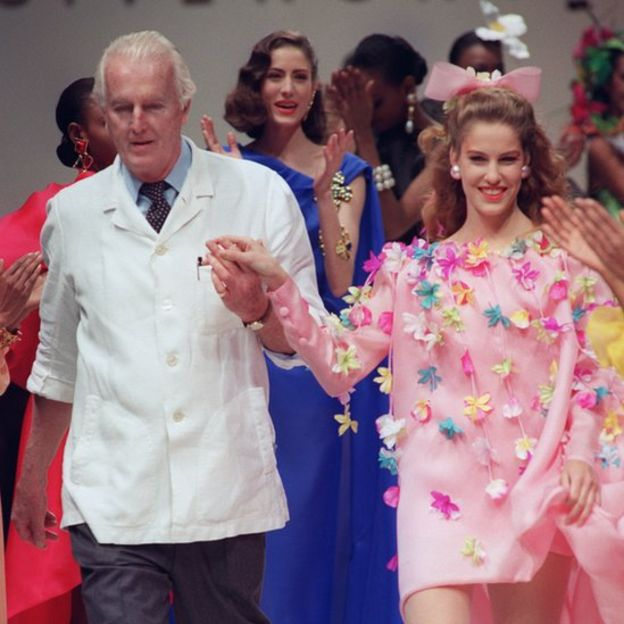 Hubert de Givenchy walks down catwalk with a model in floral Spring/Summer dress in 1991