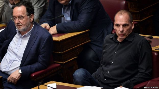 Former Greek Finance Minister Yianis Varoufakis (R) sits next to former Greek Energy Minister Panagiotis Lafazanis (L) during the vote at the Greek parliament in Athens early on July 23, 2015