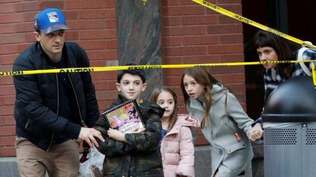 Niños y adultos pasan por los cordones policiales