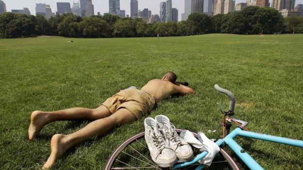 Un hombre duerme en la grama de un parque de ciudad.