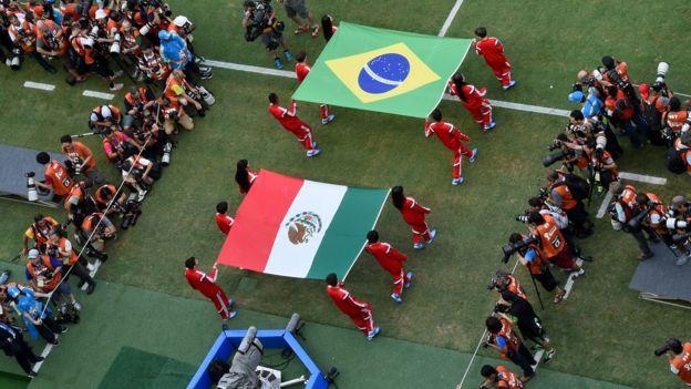 Jogadores de futebol com as bandeiras do Brasil e do México.
