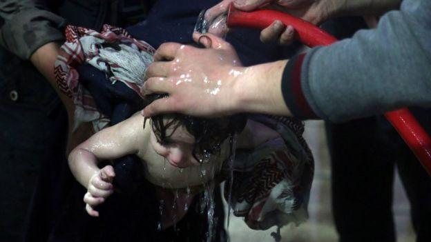 Criança é lavada na tentativa de eliminar traços de supostos agentes químicos após ataque na cidade de Douma
