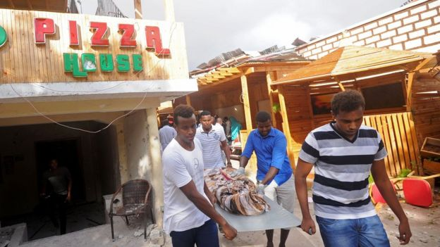 People carrying a body bag after the attack
