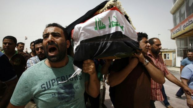 Iraqi men carry a coffin in the holy Iraqi city of Najaf on July 3, 2016