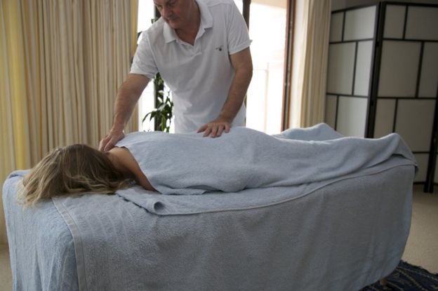 Colin Richards, Intimacy Matters sexual therapist, gives a massage to a woman lying on a stretcher. (Photo: courtesy of Colin Richards / Intimacy Matters)