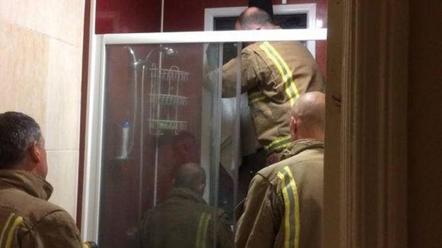Los miembros del Servicio de Bomberos y Rescate de Avon en acción, tratando de sacar a la mujer atrapada en la ventana.