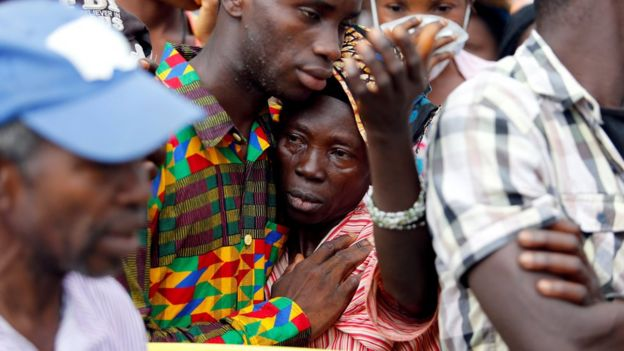 Woman is comforted after learning she has lost her son, in Freetown, on 16 August 2017
