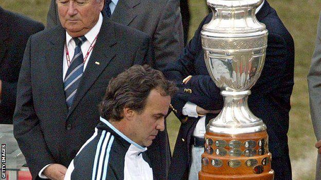 Marco Bielsa pasa frente al trofeo de la Copa América.