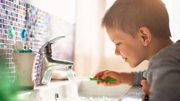 Un niño lavando su cepillo de dientes