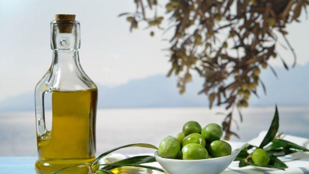 Botella de aceite de oliva y un plato con aceitunas