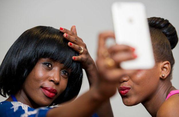 Wanawake wawili wakipiga selfie kabla ya fesheni ya swahili mjini Dar es Salaam, Tanzania tarehe 4 Disemba 2015