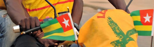 A motorbike flying Togolese flags