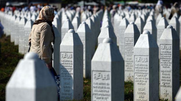 Mujer caminando frente a filas interminables de lápidas con los nombres de las víctimas de Srebrenica