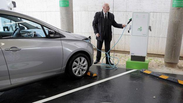 Hombre cargando carro eléctrico