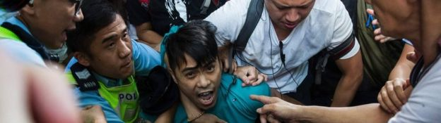 A pro-Beijing supporter is forcibly removed by police as he tries to stop a League of Social Democrats protest in Hong Kong, 1 July 2017