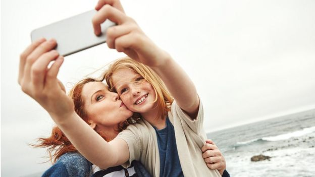girl and mother using cellphone