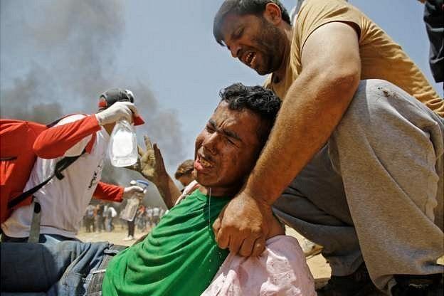 Палестинец поднимает раненого товарища