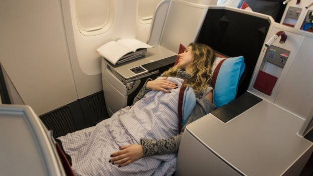 A woman sleeps in a first class seat of an airplane