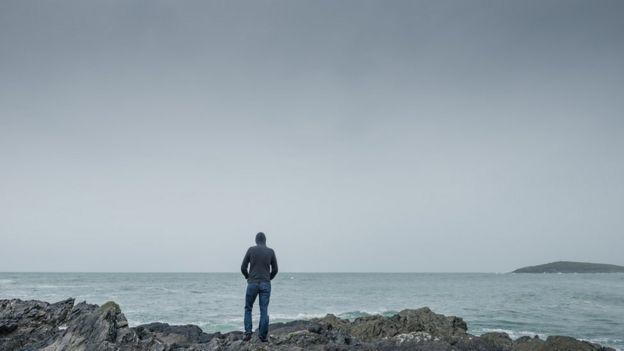 Hombre de espaldas frente al mar