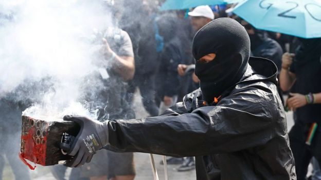 A masked protester launches fireworks in the direction of riot police during a protest on July 7, 2017 in Hamburg, northern Germany, where leaders of the world's top economies gather for a G20 summit.