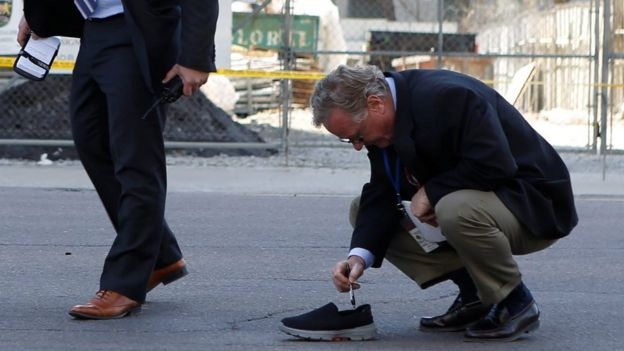 An investigator plays with a pen an abandoned shoe at the scene of the event.