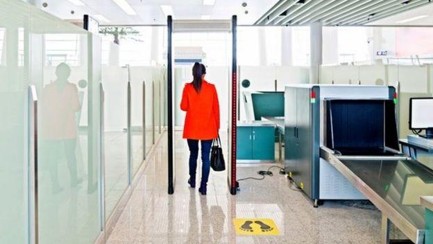 Una mujer pasa por debajo de un arco de seguridad en el aeropuerto.