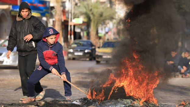 Palestinian youths set tyres on fire in Gaza City on 7 December 2017