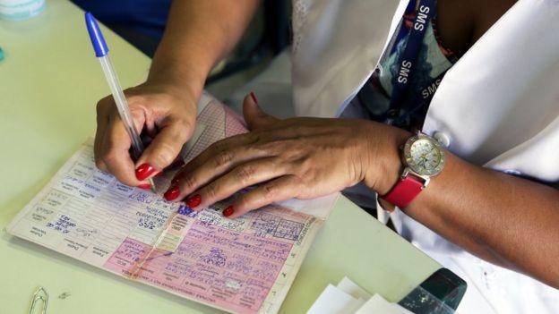 Mulher preenche carteira de vacinação