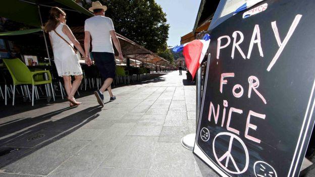 Una pareja pasa frente a un letrero de solidaridad con Niza