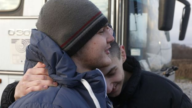 Ukrainian prisoners hug each other during a prisoner exchange in eastern Ukraine